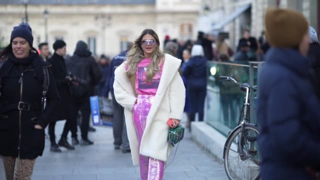 thassia naves wears sunglasses, a pink t-shirt with a printed picture, a white long fluffy winter coat, pink/purple shiny sequined glitter flare... - paris fashion week - haute couture spring/summer 2020点の映像素材/bロール