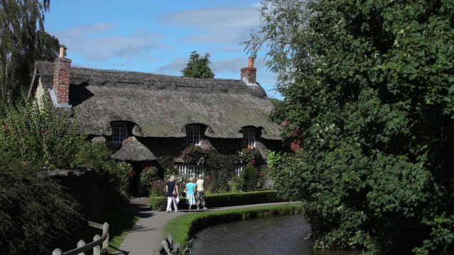 thatched cottage by river in thornton-le-dale - strohdach stock-videos und b-roll-filmmaterial