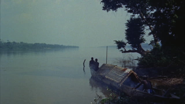 ws  thatched covered longboat in river - galeere stock-videos und b-roll-filmmaterial