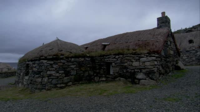 vídeos de stock e filmes b-roll de a thatched roof covers a stone house in gearrannan scotland. available in hd. - hébridas