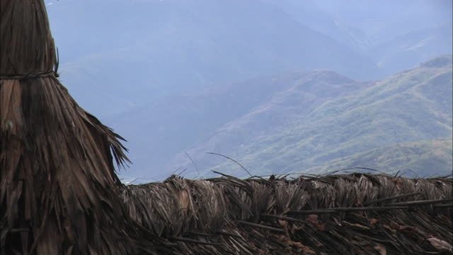 a thatched roof frames lush, rolling hills in india. - strohdach stock-videos und b-roll-filmmaterial
