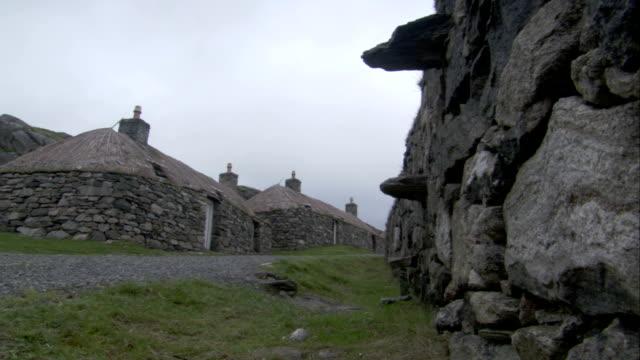 vídeos de stock e filmes b-roll de thatched roofs cover stone cottages in black house village in gearrannan scotland. available in hd. - telhado de palha