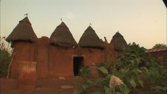 thatched spires line the roof of an adobe house in benin. - thatched roof stock videos & royalty-free footage
