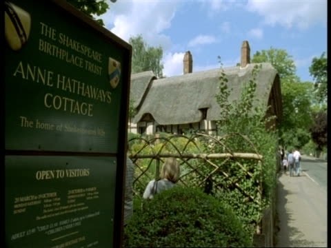 thatched tudor cottage, stratford-upon-avon - information sign in foreground, tourists outside anne hathaway's house (wife of shakespeare) - tetto di paglia video stock e b–roll