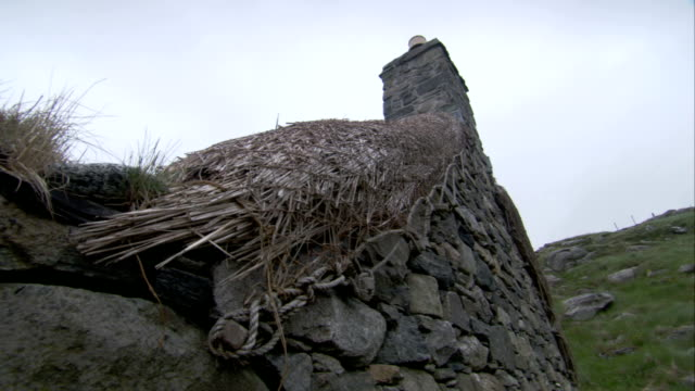 thatching covers the roof of a stone house. available in hd. - stone house stock videos & royalty-free footage
