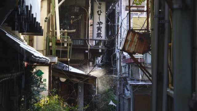 thaw water drips from roof to alley among the ryokan (traditional japanese inn) along the alley at shibu onsen (shibu hot spring) yamanouchi-machi, nagano japan on feb. 18 2019. - tourism点の映像素材/bロール
