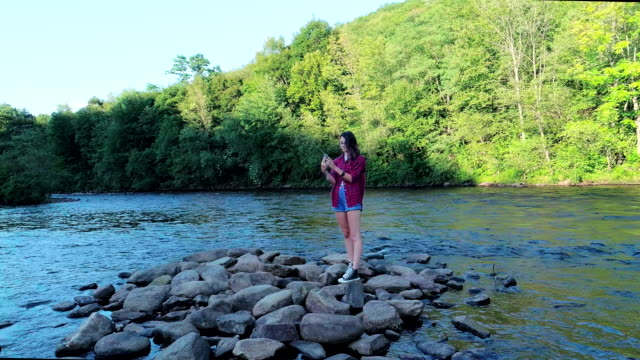 Die 16-jährige Teenager Mädchen machen Selfiein Vorderseite des He malerischen Blick auf die Lehigh River in der Nähe von Jim Thorpe, Pennsylvania, bei Sonnenuntergang. Luftbild-Drohne Video.