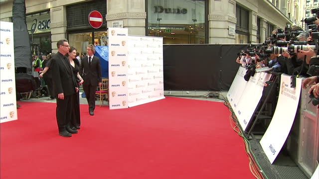the 2010 baftas held at the royal opera house, london. shows exterior shots of mark kermode and wife linda ruth williams posing for photographers on... - マーク カルモード点の映像素材/bロール
