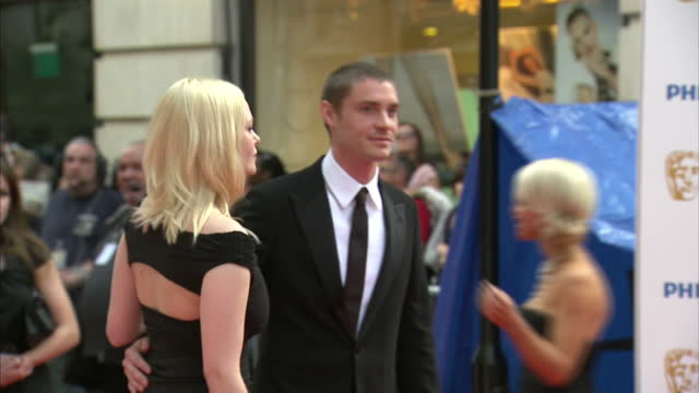 the 2010 baftas held at the royal opera house london shows exterior shots of anabelle horsey and max brown posing for photographers on the red carpet - horsey england bildbanksvideor och videomaterial från bakom kulisserna