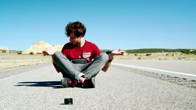 vidéos et rushes de le 30 ans, hipster, vlogger, posant devant la caméra d'action lorsqu'il est assis sur la route dans l'utah, aux états-unis. - endroit isolé