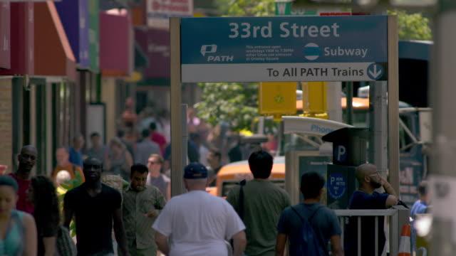 vídeos de stock, filmes e b-roll de cu of the 33rd street path train entrance on 6th avenue.  the surrounding sidewalk is bustling with people. - passagem subterrânea via pública