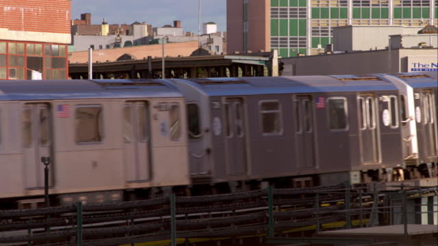 the 7 elevated subway train pulls into the station in long island city new york. - hochbahn passagierzug stock-videos und b-roll-filmmaterial