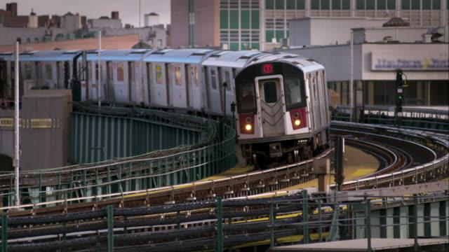 the 7 elevated subway train rounds a corner and leaves the station in long island city new york. - högbana bildbanksvideor och videomaterial från bakom kulisserna