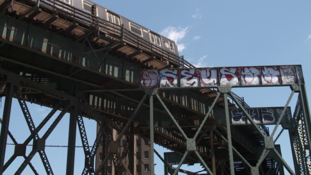 the 7 subway train makes a turn on a elevated track painted in graffiti in new york city. - elevated train stock videos & royalty-free footage
