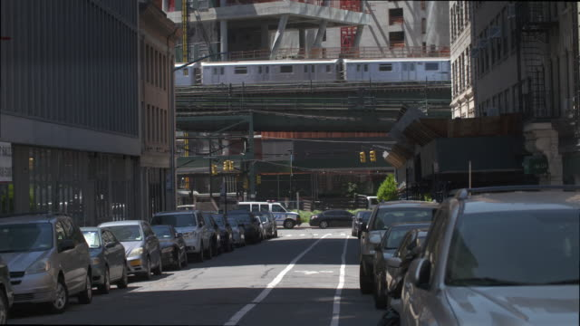 the 7 subway train travel on elevated track a city scene and traffic leads up to the train. - elevated train stock videos & royalty-free footage