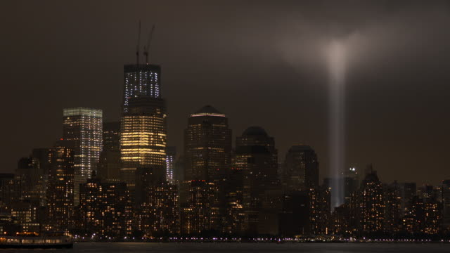 The 911 memorial lights light up the downtown skyline.   A ferry travels in front