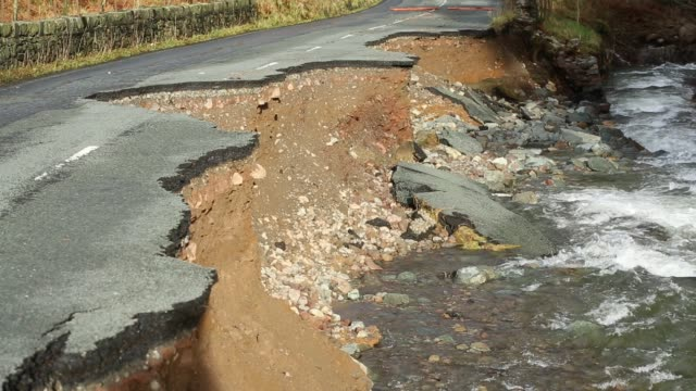 stockvideo's en b-roll-footage met the a591, the main road through the lake district, completely destroyed by the floods from storm desmond, cumbria, uk. the road was breached in... - bord weg afgesloten