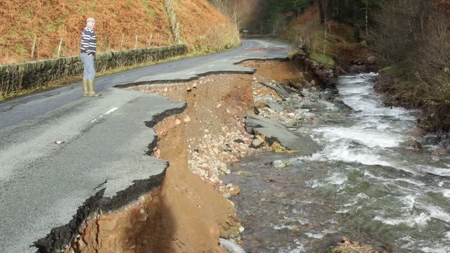 The A591 the main road through the Lake District completely destroyed by the floods from Storm Desmond Cumbria UK The road was breached in several...