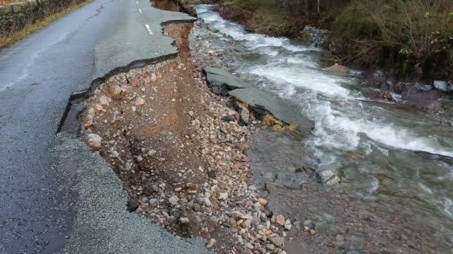 the a591, the main road through the lake district, completely destroyed by the floods from storm desmond, cumbria, uk. the road was breached in... - road closed englisches verkehrsschild stock-videos und b-roll-filmmaterial