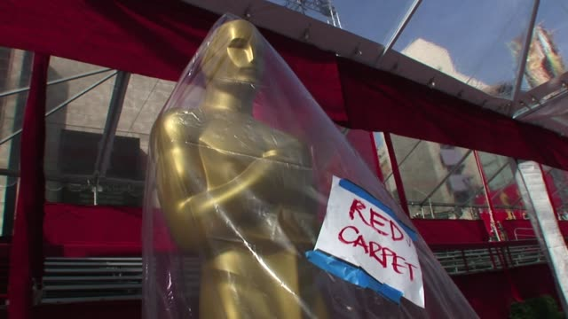 The Academy Award preparation for the Oscar showing an Oscar statue covered in plastic blowing in the wind with a red carpet sign before its...