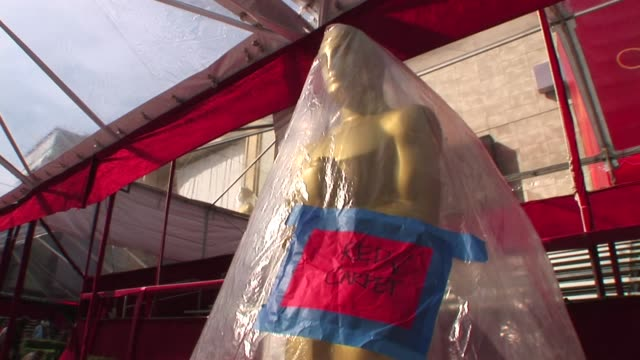 the academy award preparation for the oscar showing an oscar statue covered in plastic blowing in the wind with a red carpet sign before its... - skulptur kunstwerk stock-videos und b-roll-filmmaterial
