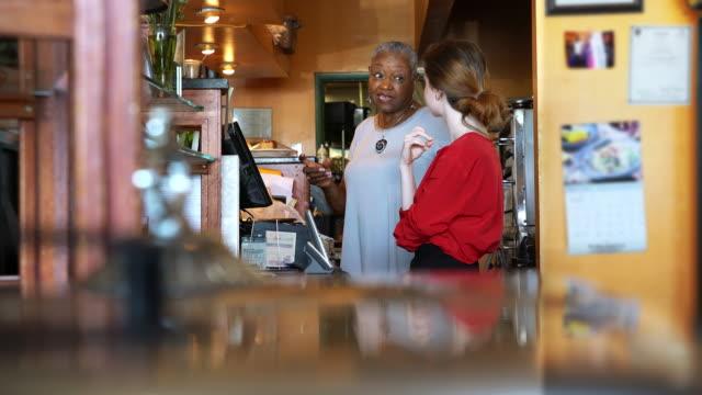die aktive und positive senior 77 jahre alt schwarze geschäftsfrau lehre der jungen kaukasische weiße mädchen gewusst wie: verwenden sie die registrierkasse im restaurant - teenager alter stock-videos und b-roll-filmmaterial