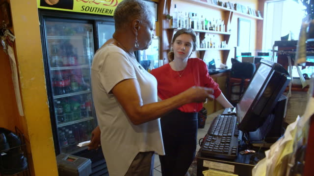 The active, positive senior 77-years-old black businesswoman teaching the young Caucasian white girl how to use the cash register in the restaurant