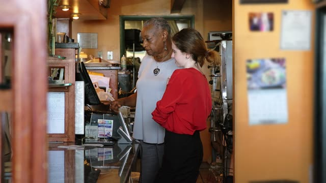 the active, positive senior 77-years-old black businesswoman teaching the young caucasian white girl how to use the cash register in the restaurant - trainee stock videos & royalty-free footage
