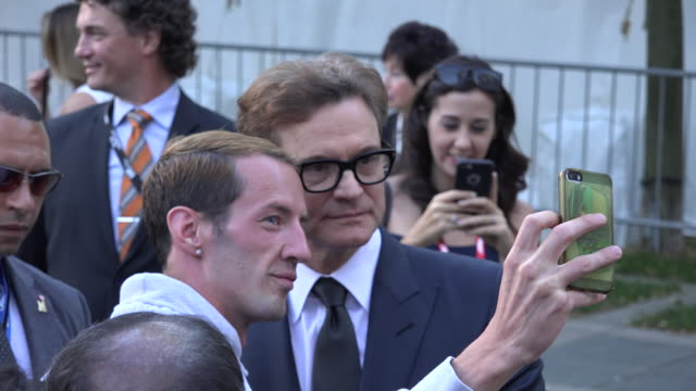 vídeos de stock, filmes e b-roll de the actor leaves the red carpet to greet the fans gathered outside - colin firth