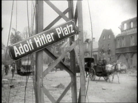 the adolf hitler platz street sign hangs from a post while horsedrawn carriages drive through ruined berlin germany - 1945 stock-videos und b-roll-filmmaterial