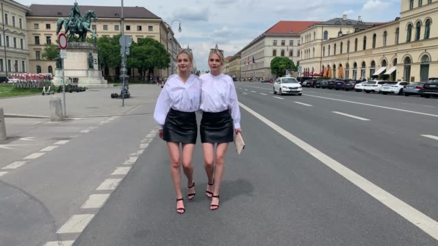 the advertising twins julia meise and nina meise wearing white blouses by aybi, black leather skirts by h&m, black sandals by h&m and sunglasses by... - street style点の映像素材/bロール