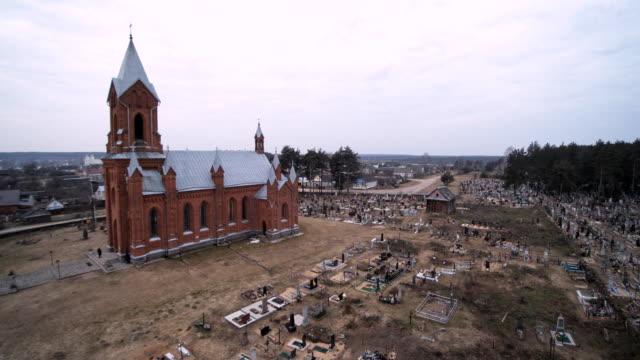 vídeos de stock, filmes e b-roll de a vista aérea zangão da catedral católica do saint aliaksey, séculos xix-xx, o ivyanets cidade, bielorrússia, europa de leste. - tijolo material de construção