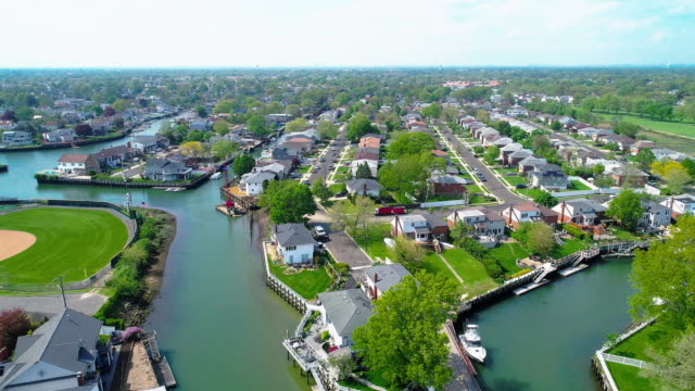 the aerial drone view to a wealthy residential district in oceanside, queens, new york city, with houses with pools on backyards and piers with boats along the channels. forward camera motion. - long island video stock e b–roll