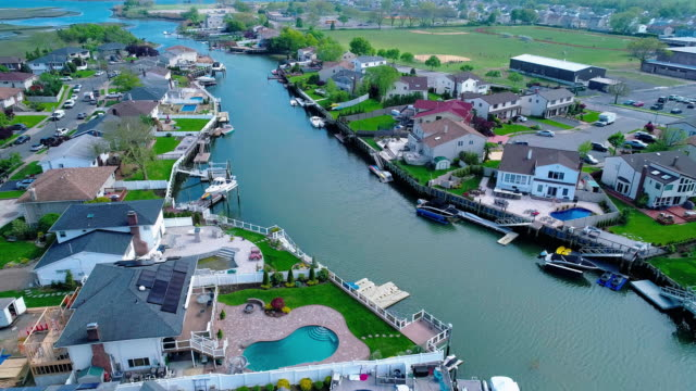 the aerial drone view to a wealthy residential district in oceanside, queens, new york city, with houses with pools on backyards and piers with boats along the channels. accelerated timelapse-style complex forward and tilting down camera motion. - nassau stock videos & royalty-free footage
