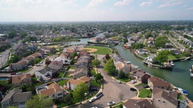 vidéos et rushes de la vue de drone aérien à un quartier résidentiel riche dans oceanside, queens, new york city, avec des maisons avec des piscines sur des arrière-cours et des piliers avec des bateaux le long des canaux. mouvement de caméra descendant. - queens