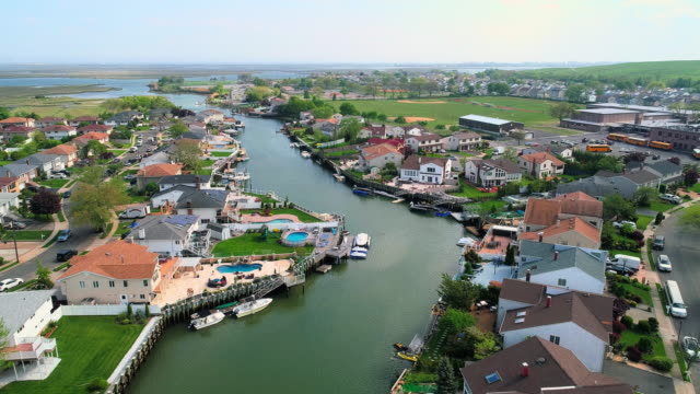 the aerial drone view to a wealthy residential district in oceanside, queens, new york city, with houses with pools on backyards and piers with boats along the channels. forward camera motion. - queens video stock e b–roll
