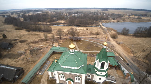 die luftbild-drohne ansicht zur orthodoxen kirche in dem kleinen dorf vishnevo, belarus, osteuropa - fahrstuhlperspektive stock-videos und b-roll-filmmaterial
