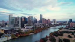 The aerial drove view of Austin Downtown, Texas, USA, from Auditorium Shores at Town Lake Park across Colorado River. Aerial drone video with the panoramic camera motion.