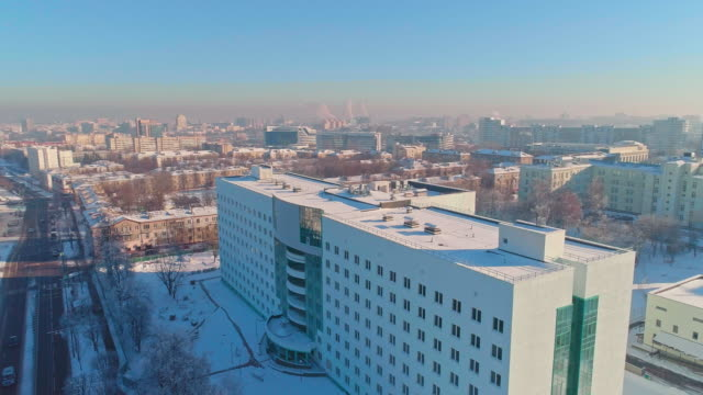 The aerial panoramic view on the winter city covered by the snow in the bright cold sunny day. Orbit camera motion.