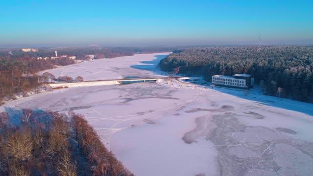 vídeos de stock, filmes e b-roll de a aérea cênica vista panorâmica sobre o rio congelado e a floresta ao pôr do sol. - bielorrússia