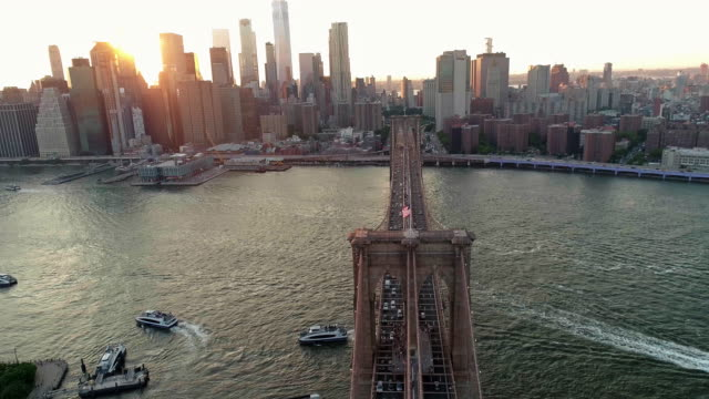vidéos et rushes de la vue aérienne panoramique à manhattan downtown et brooklyn bridge de brooklyn heights, sur l'east river au coucher du soleil. motion descendante et ascendante. - pont de brooklyn