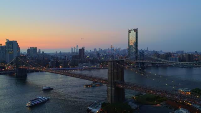 空中からの眺めマンハッタン ダウンタウンとブルックリン ブリッジに夕日を東川に架かるブルックリン ハイツ。橋に沿ってパノラマ スローモーション