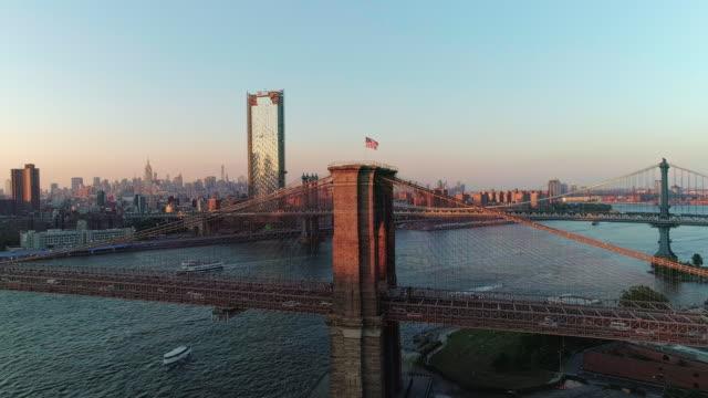空中からの眺めマンハッタン ダウンタウンとブルックリン ブリッジに夕日を東川に架かるブルックリン ハイツ。昇順スローモーション。