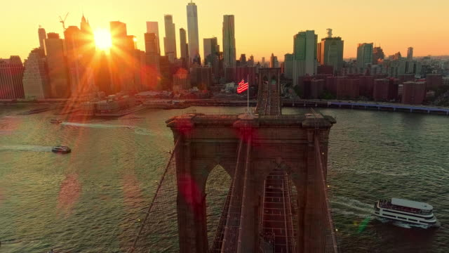 The aerial scenic view to Manhattan Downtown and Brooklyn Bridge from Brooklyn Heights over the East River at the sunset. Combined forward - climbing camera motion.