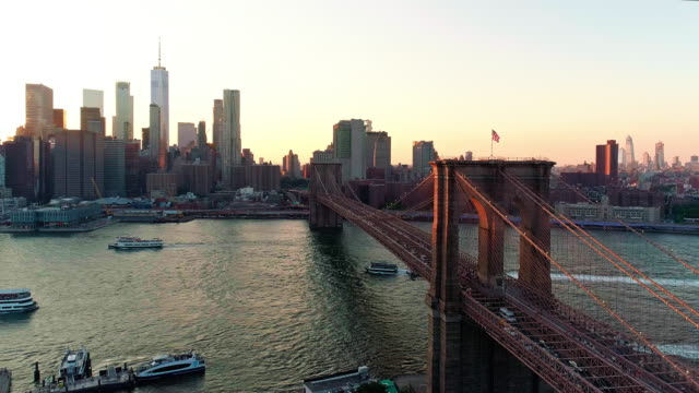 die malerische luftbild downtown manhattan und brooklyn bridge aus brooklyn heights über den east river in den sonnenuntergang. - new york stock-videos und b-roll-filmmaterial