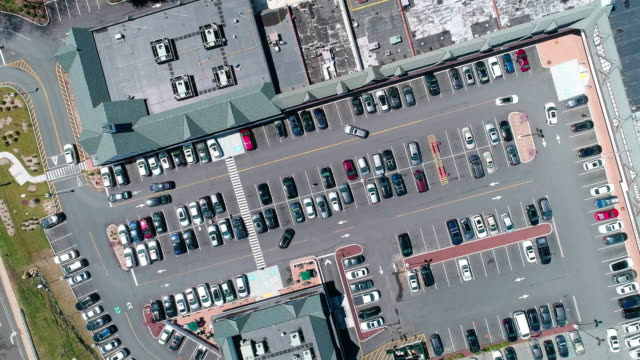 the aerial video of the traffic at the parking lot of the shopping mall in the small american town - car park stock videos & royalty-free footage