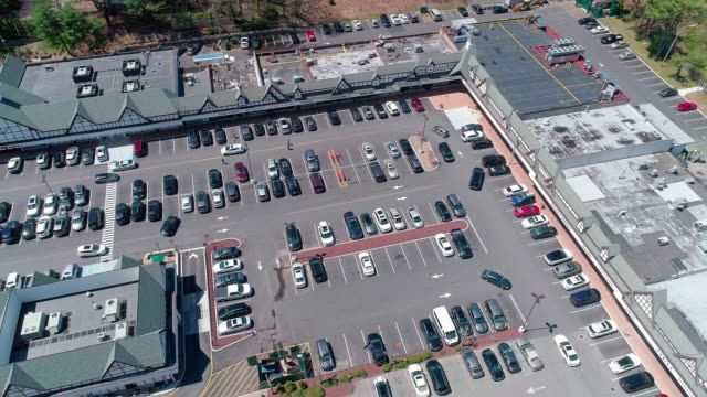 the aerial video of the traffic at the parking lot of the shopping mall in the small american town - stati del mid atlantic usa video stock e b–roll