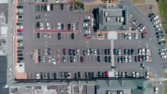the aerial video of the traffic at the parking lot of the shopping mall in the small american town - parcheggio video stock e b–roll