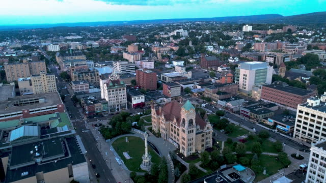 stockvideo's en b-roll-footage met de luchtfoto van lackawanna county courthouse square met soldaten en zeilers monument, elektrisch gebouw, en downtown district van scranton bij zonsondergang. pennsylvania, usa. aerial drone video met de voorwaartse camerabeweging. - pennsylvania