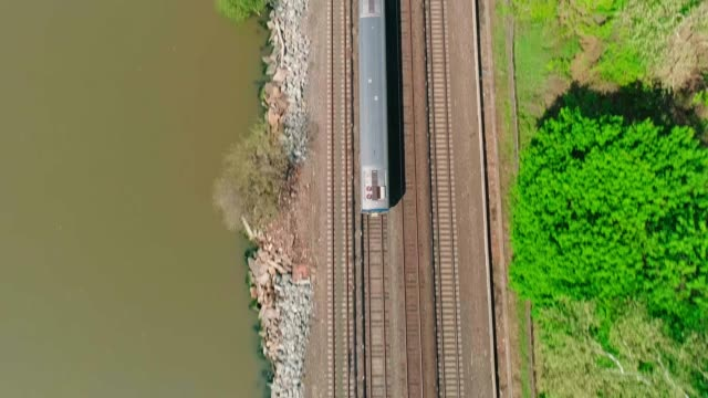 The aerial view of the passenger train passing along the Hudson River near by Dobbs Ferry, Westchester County, New York, USA